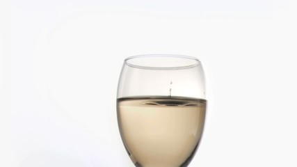 A drop falling in super slow motion in a wine glass