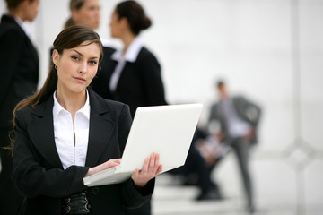 Businesswoman with laptop stood outside workplace