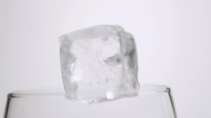 An ice cube in super slow motion falling in a glass