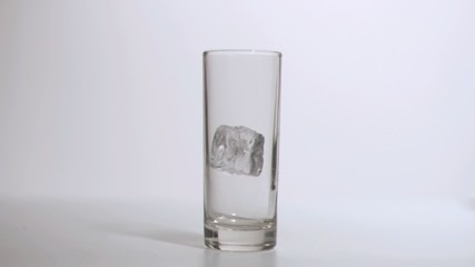 Glass in super slow motion receiving an ice cube