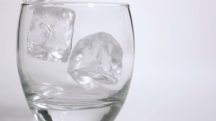 Ice cubes in super slow motion put in a tumbler