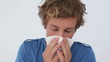 Sick man sneezing into a tissue