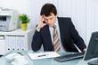 mitarbeiter sitzt gestresst am schreibtisch