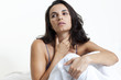 Schöne Frau mit Halsschmerzen im Bett sitzend