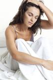 Schöne Frau mit Kopfschmerzen im Bett wacht auf