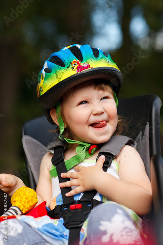 Little girl in the seat bicycle with a helmet on his head