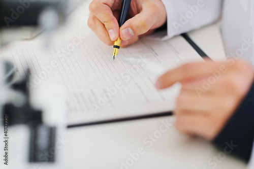 Closeup writing in document hands of medical doctor