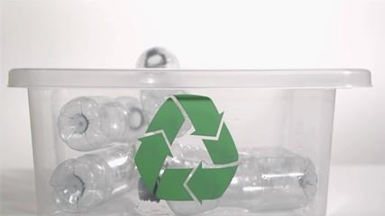 Plastic bottles falling in super slow motion into a recycling bin