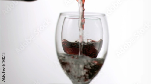 Wine and water filling in super slow motion glasses