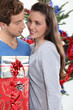 Young man offering gift to his girlfriend for Christmas