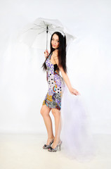 Beautiful girl with white umbrella and transparent tail stands i