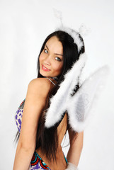 Young beautiful girl with white wings wearing dress smiles
