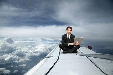 Businessman sat on the wing of an airplane