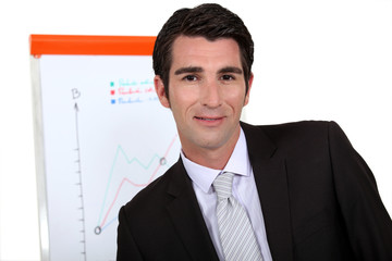 Businessman standing next to a flip chart