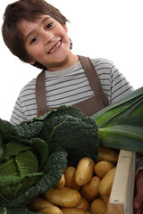 child standing behind vegetables