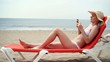 Young woman using cellphone while lying on sunbed on beach