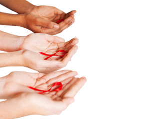 hands holding red ribbon to rise AIDS HIV awareness