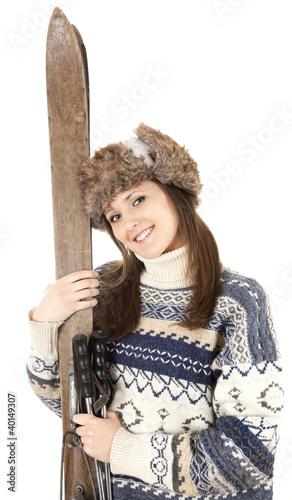 smiling girl in winter clothes holding old wooden skis
