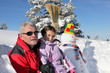 Father and daughter stood by snowman