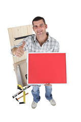 Handyman holding a red sign