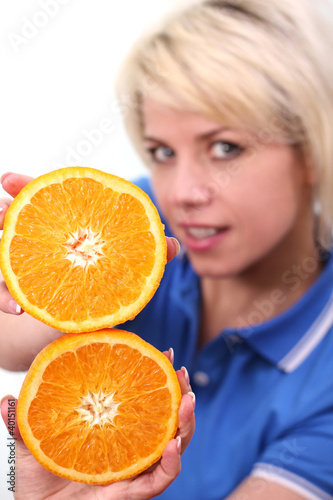 Young woman holding a slice of orange on white background.