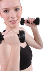 Young woman using dumbbells