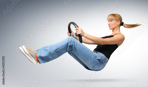 Young girl car driver with a wheel, concept