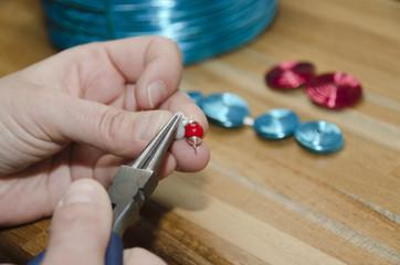 mains de femme créant un bijou de mode