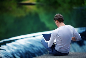Man with laptop sitting over the waterfall