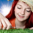 Girl with straw hat trims the synthetic turf with nail scissors
