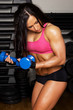 Woman is holding blue dumbbells