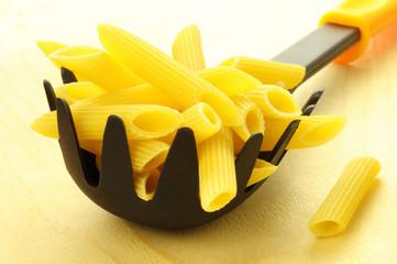 Italian penne pasta in a spaghetti server - wooden background