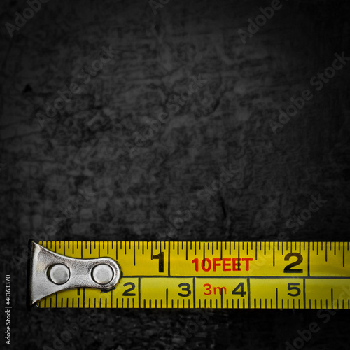 Measuring tape on a black metallic background