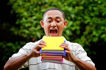 ethnic young man try to eat stack of books