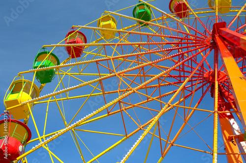 Leinwanddruck Bild Colorful ferris wheel and blue sky