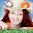 Teenager with flower hat cuts grass with nail scissor