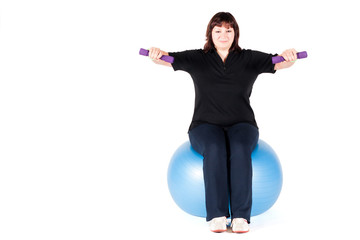 Shot of a overweight young woman exercise on fitness ball agains
