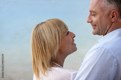 Mature couple smiling at the seaside
