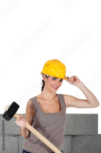 Woman with helmet and mallet in hand
