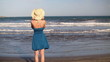Woman in blue dress standing by the sea, slow motion