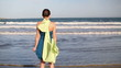 Woman in blue dress and sarong standing by the sea, slow motion