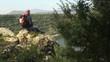 Adult man with binoculars sitting on rock, looking at lake