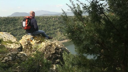 Adult man with binoculars sitting on rock, looking at lake