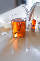 Glass mug with tea, teapot en teabag on table