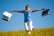 Junge blonde Frau in der Wiese mit Einkaufstaschen im Frühling
