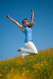 Junge vitale Frau hüpft in die Luft im Frühling