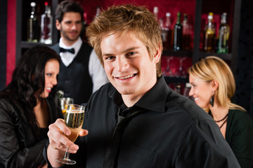 Young man at the bar drink champagne