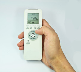 Hand is holding a remote control of air conditioner isolated