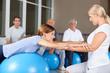 Fitnesstrainerin hilft Frau bei Rückenübung