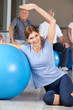 Frau macht Rückenübung mit Gymnastikball